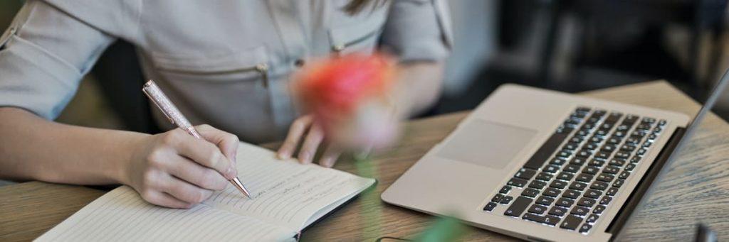 Vrouw schrijft naast laptop