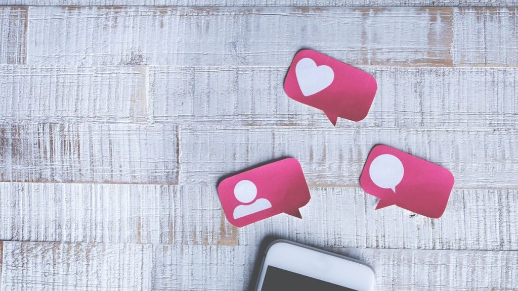 witte smartphone met roze symbolen