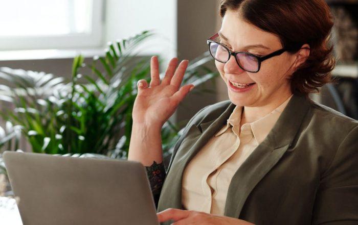 Vrouw zwaait naar webcam