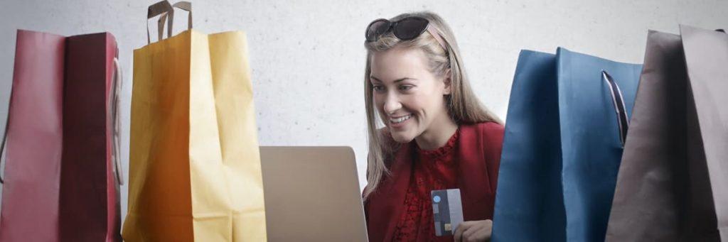 vrouw met laptop, creditcard en shopping tassen